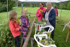 Maja Elf och Tova Magnusson får hjälp att smycka midsommarstången av Rimor Rylner och Ewa Magnusson