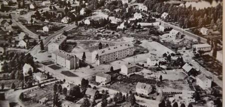 En 60 år gammal bild från Vaggeryd visar de sista spåren av Kalvdalen i kvarteret Staren där tre köpingsägda hyreshus nyss är uppförda. Korpgatan håller på att skapas. Till höger riksväg 1, blivande E4, i övre högra hörnet Hjortsjön södra del.